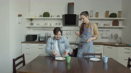 dispute : Angry husband sitting at kitchen table not wanting scrambled eggs for breakfast insulting prepared meal wife, accusing of failing to cook tasty. Aggressive man starting family conflict for nothing. Stock Footage