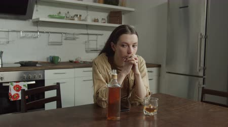 abandonment : Lonely thoughtful woman spending evening with bottle of whiskey while husband cheating on her with mistress. Abandoned young wife thinking about divorce sitting alone next to silent smartphone.