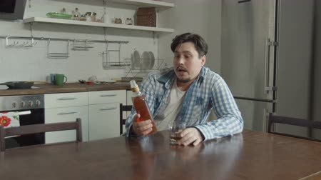 abandonment : Abandoned husband drinking alcohol beverage in despair while sitting at kitchen table alone after breakup. Depressed drunk man pouring whiskey into glass, lamenting collapse of family relationships. Stock Footage