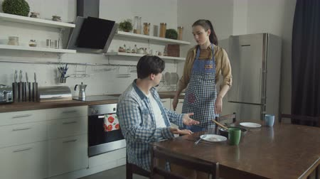 кризис : Disgruntled man sitting at kitchen table attacking wife with complaints about prepared breakfast. Irritated husband with disgust looking at scrambled eggs, swearing, offending woman with his behavior.