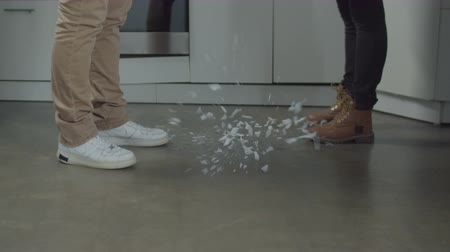 přestupek : Close-up of white plate breaking into small pieces while falling on kitchen floor during couple swearing symbolizing breakup of family. Family relationships do not glue like broken plate. Dostupné videozáznamy