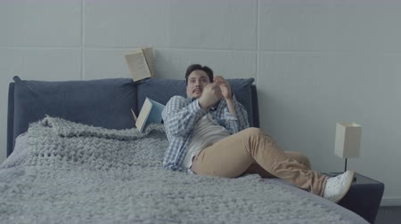 annoyance : Angry woman tired of doing household chores throwing book at dreamy husband sitting back on bed in bedroom. Aggressive man screaming at wife trying to attract his attention and needed help. Stock Footage