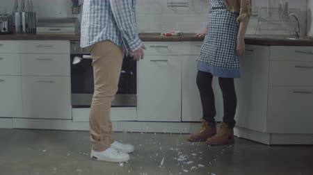 jealous : Close-up of plate falling on floor and breaking into small pieces during domestic quarrel between jealous husband and offended wife. How not to glue broken plate so not to connect breaking up couple.