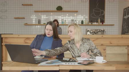 remotely : Concentrated on work female business partners sitting at cafe table viewing laptop screen agreeing with calculations. Serious businesswomen drinking coffee and working remotely in city cafe. Stock Footage
