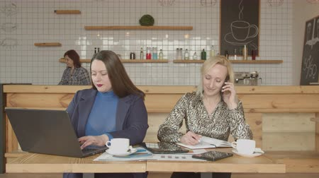 femininity : Focused on work independent businesswomen networking online with laptop and smartphone sitting at cafe table. Successful female business colleagues working remotely during coffee break in cafe.