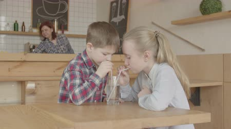 lemoniada : Cheerful little girl with long blonde hair and short cut boy having fun gurgling while drinking from one glass through straws. Cute elementary age friends enjoying company at meeting in cafe.