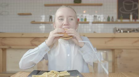 greedily : Close-up of cute preadolescent child enjoying unhealthy meal sitting at cafe table. Little blonde girl in white blouse eating greedily hamburger, plate full of french fries, kid loving fast food.