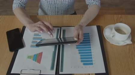 remotely : Close-up of businesswoman holding tablet pc and analyzing charts on printouts while working at project start-up in cafe. Top view of female hands checking indicators on graph with data on tablet. Stock Footage