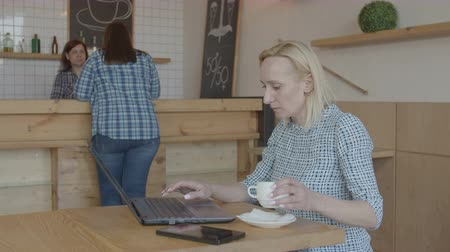 блог : Focused female freelancer typing on laptop pc editing new video for blog while drinking coffee and sitting at cafeteria table. Adult woman blogger networking online starting up new internet project.