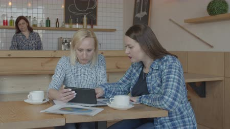 nőiesség : Serious females entrepreneurs working remotely brainstorming during start-up of business project. Confident women freelance using tablet and charts communicating at meeting in coffee shop. Stock mozgókép
