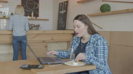 remotely : Serious woman it programmer using laptop while working remotely at cafeteria table. Successful female creating source code while eating unhealthy fast food and networking online on laptop pc in cafe.