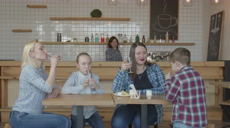 harcama : Two single mothers spending leisure with preadolescent kids sitting at cafe table. Joyful adults and children having fun, chatting, eating, drinking, clinking glasses with each other and all together. Stok Video