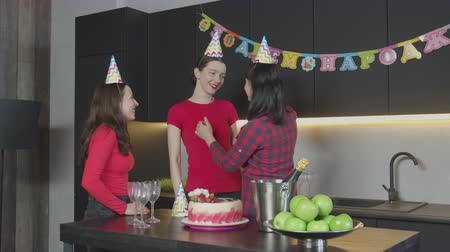 meia idade : Joyful middle aged mother adjusting party hats to lovely daughters, preparing celebration of Birthday at home. Happy women wearing cone caps celebrating anniversary in festively decorated kitchen.