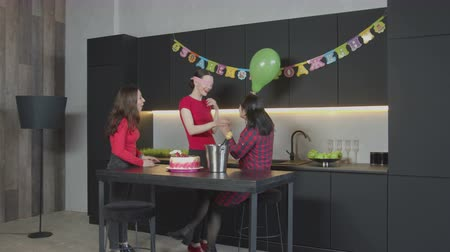 díszített : Cheerful adult female enjoying celebration of Birthday in narrow circle with mother and good friend in festively decorated kitchen. Prepared for surprise blindfolded female groping and hugging mom. Stock mozgókép