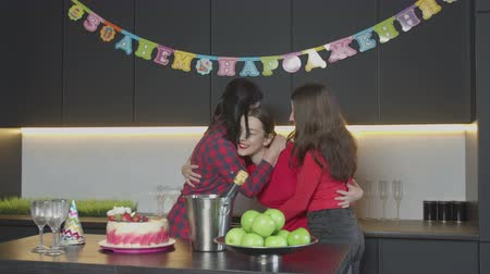 átölelő : Happy carefree birthday girl enjoying embrace and kisses of mother and best friend during celebration of thirtieth anniversary in narrow circle. Pretty woman accepting congratulations in home kitchen. Stock mozgókép