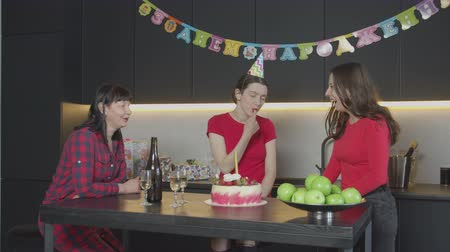 impatience : Happy females sitting at kitchen table with champagne and birthday cake waiting for late guest. Impatient mischievous adult birthday girl in cone party hat tasting by finger cream on holiday cake.