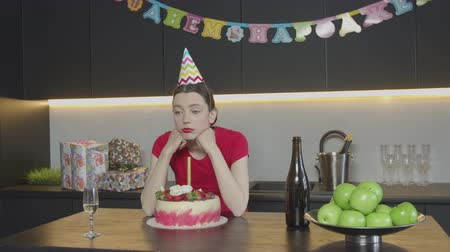 yokluk : Disappointed by absence of guests at her Birthday pretty female drinking champagne sitting at kitchen table alone. Attractive upset woman celebrating her 30th anniversary in loneliness at home. Stok Video