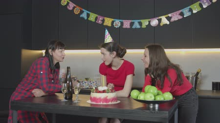 impatience : Ready for birthday celebration females having fun waiting for late guest in festively decorated kitchen. Middle aged mother jokingly beating daughters playful hands trying with fingers cream on cake.