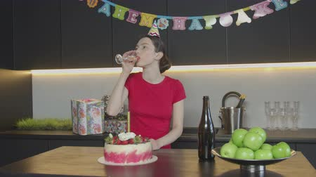 конусы : Unhappy woman in party hat pouring and drinking champagne celebrating birthday alone in festive decorated kitchen. Pretty female disappointed because nobody came to celebrate her anniversary. Стоковые видеозаписи