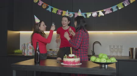 champagne bottles : Positive females in cone hats cklinking glasses, drinking champagne while performing funny dance during birthday celebration in festive homey atmosphere. Happy family enjoying party in kitchen. Stock Footage