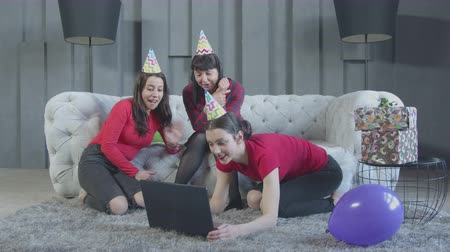 remotely : Joyful adult birthday girl video chatting online using laptop sitting on floor while mom and sister joining to conversation on background. Smiling family in party hats waving hands during video call. Stock Footage