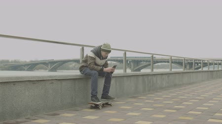 bruslař : Teenage boy in headphones holding cellphone and listening to music while sitting on parapet of river embankment. Young skateboarder taking musical break in skating waiting for best friend.