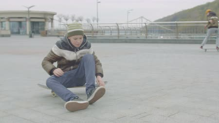 cipőfűző : Close-up of teenage skateboarder sitting on skate and tying shoelaces on sneakers while his friend doing manual trick on background. Active teenagers rolling on skateboards around city square.