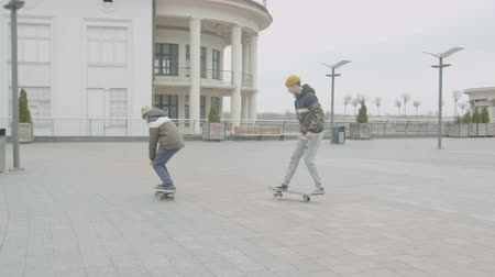 hops : Teenage skaters learning to do rolling off a drop and manual tricks skateboarding on city street. Warmly dressed teenage beginners practicing manual, doing hops and rolling off drop skating outdoors. Stock Footage
