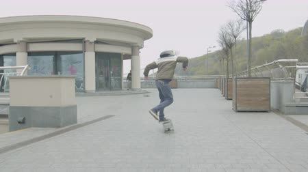 skateboard : Teen skaters learning doing shuvit tricks, pumping on skateboard sliding down the edge of stairs. Two friends rolling on skates, pushing with feet, practicing skateboard tricks, skating on sidewalk. Stock Footage