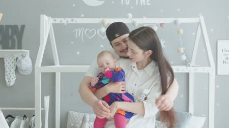 újszülött : Caring father embracing, kissing beloved daughter and wife holding cute infant in childrens room. Cheerful family spending leisure together, communicating with toddler girl in homey atmosphere.