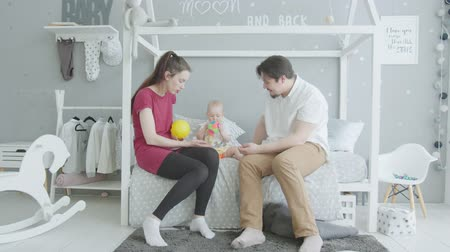 Çocuk bakımı : Active infant girl performing funny dance with toy ball sitting on bed. Joyful family playing with toddler daughter taking colorful ball from moms hands and making amusing movements like dancing.