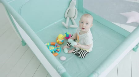 Çocuk bakımı : Top view of cheerful toddler child sitting in playpen among toys enjoying play in childrens room in loneliness. Adorable infant girl playing toys and looking up from playpen waiting for parents.