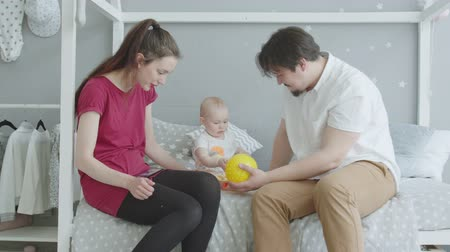 puericultura : Cute baby actively banging toy balls with hands, bitting on bed rejoicing play in bedroom together with mom and dad. Happy parents watching toddler daughter playing colorful toys with delight. Stock Footage
