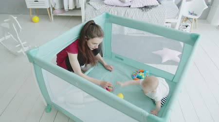 puericultura : Active infant trying to get up playing toys crawling around playpen in nursery. Joyful mom sitting near playpen with cute baby daughter having fun playing, happy motherhood and childhood. Stock Footage