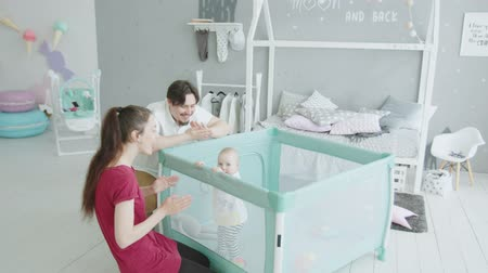 Çocuk bakımı : Joyful infant girl standing by herself holding on to edge of playpen and looking at mom and dad clapping hands and imitating animals. Cute toddler daughter enjoying funny play with beloved parents.