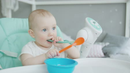 Çocuk bakımı : Close-up of teether toddler girl sitting on feeding chair in front of empty plate and gnawing plastic spoon. Cute infant teething and biting spoon before eating on chair for babies in childrens room.