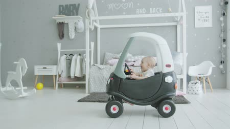 рог : Cute toddler child trying to drive baby car, turning steering wheel, pushing horn enjoying play in nursery at home. Adorable infant playing sitting in car designed for development of children.