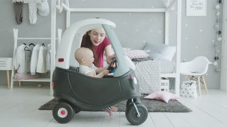 crying baby : Playful mother trying to cheer crying infant girl sitting in baby car at home. Upset toddler daughter holding steering wheel and angry at not driving car while mom pushing horn and imitating movement.