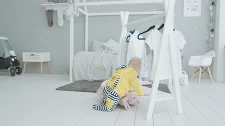 получать : Active infant girl standing on knees wearing on head clothes from rack and learning to get up at home. Curious toddler child trying to wear clothing hanging on rack exploring world indoors.
