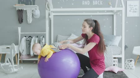 plazí : Sporty slim woman exercising with infant daughter on fitness ball in nursery. Cute toddler girl trying crawling, lying on big purple fitball while mom swinging her by legs during workout at home.