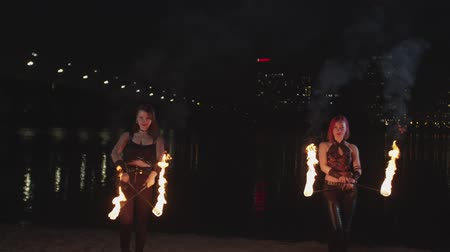 tocha : Young women jugglers performing magic motion and energy of flame during fireshow on riverside. Fascinating spectacle of burning torches in skillful hands of females fireshow artists.