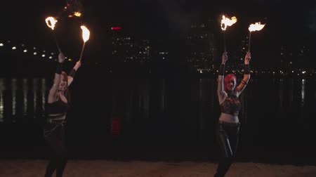 fireshow : Young women performing amazing fireshow with flame, juggling burning torches on river bank. Attractive female artsits dancing on sand with lit torches outdoors over night city lights in background. Stock Footage