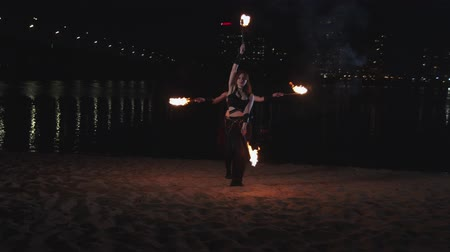 fireshow : Two young females fireshow artists performing synchronous work with torches standing on sand by riverside. Attractive firegirls showing joint juggling skills on background of night city lights. Stock Footage