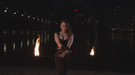 gyújtás : Young female fireshow artist in stylish black clothing performing fantastic show with flame standing near river. Firegirl juggling burning torches outdoor showing fiery mystery in lights of night city.