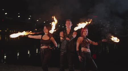 espectador : Stylish firegirls and fakir performing motion of living fire at dusk of night city. Trio of young fireshow artists standing on riverbank with burning torches hypnotizing viewer with power of flame. Vídeos