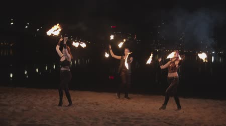 ustalık : Amazing trio of artists spinning burning staves standing on sand near river, lights of night city reflected in water. Stylish firegirls and fakir performing art of juggling during fireshow at dusk. Stok Video