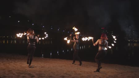 skillful : Stylish firegirls and fakir performing skill of juggling burning fans and staves turning around on sand during fireshow by river. Trio of skillful artists juggling with flame at dusk of night city.