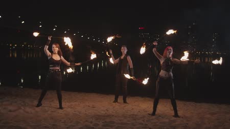 ustalık : Two attractive firegirls and handsome fakir performing wonderful juggling skills during amazing fireshow in city dusk. Skillful trio of artists juggling with burning staves standing on river bank.