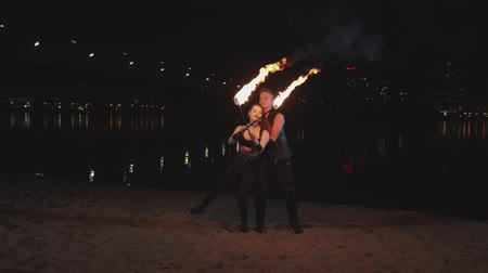 fireshow : Young couple of fireshow artists performing dance element on river bank at dusk of night city. Handsome male artist lifting woman holding crossed burning torches and spinning around at night.