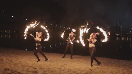 опасность : Trio of young artists performing amazing dance show with burning fire on river bank at dusk. Two firegirls and fakir juggling with burning fans and staves during dance over night city lights.